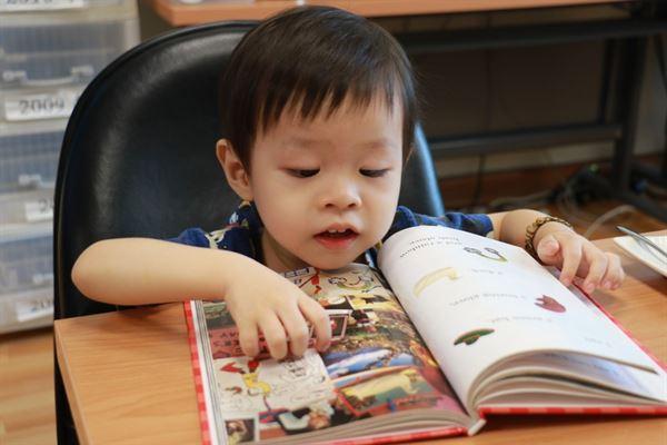 兒童看書時手伸直,是預防近視的方法之一。(圖片提供/台中慈濟醫院)