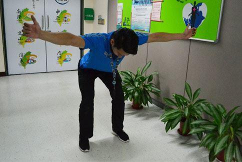 屈膝比讚操,雙腳與肩同寬,微微屈膝,雙手比出讚的姿勢自然向前、往外伸出。(攝影/洪毓琪)