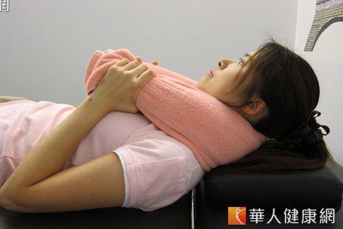 第3招:長浴巾協助起床。讓肌肉舒緩與治療。(示範/物理治療師許家榮)